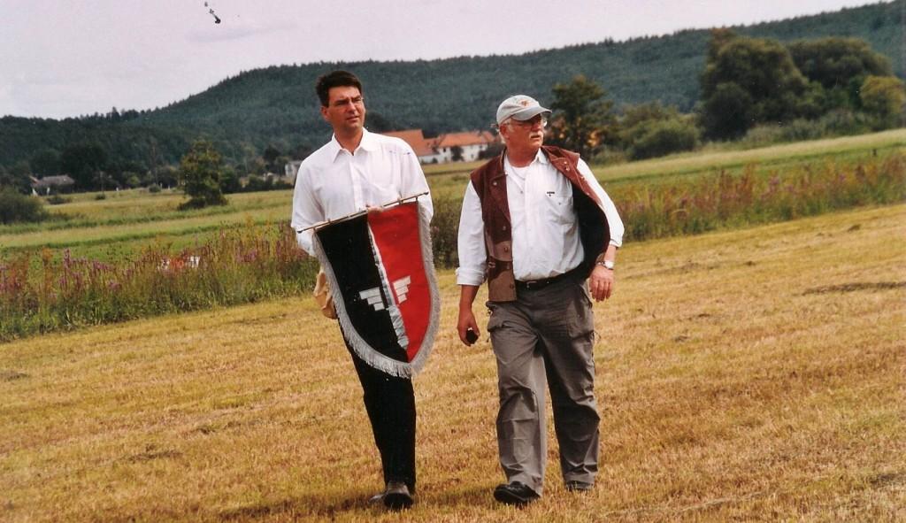Nach geglücktem Fallschirm-Fahnenabwurf bringen Armin Schrott und M.H.H.W. gemeinsam diese mit den Insignien des JG 52 zur Übergabe an unseren Ehrenvorstand W. Wolfrum und M. Leisebein.