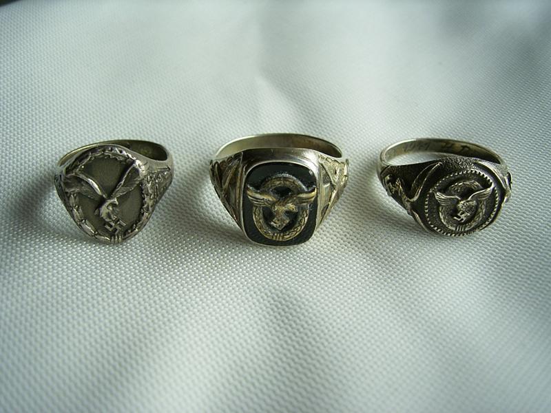 Der mittlere Ring ist der gängigste Ring für Flugzeugführer. Ring in Silber, eingearbeitete Onyxplatte, mit vernieteter 9 mm Mini-atur als Auflage. Seitlich je einen geprägten und nachgravierten Luftwaffenadler. Die beiden anderen Ringe rechts und links da- von, sind so genannte zeitgenössische Juweliersanfertigungen.